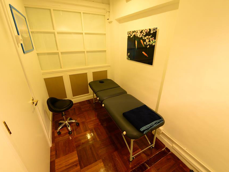 treatment room equipped with massage bed and chair
