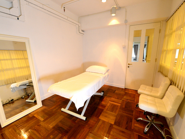 private room with standing mirror and massage bed