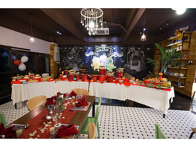 birthday party room filled with dining table and buffet food