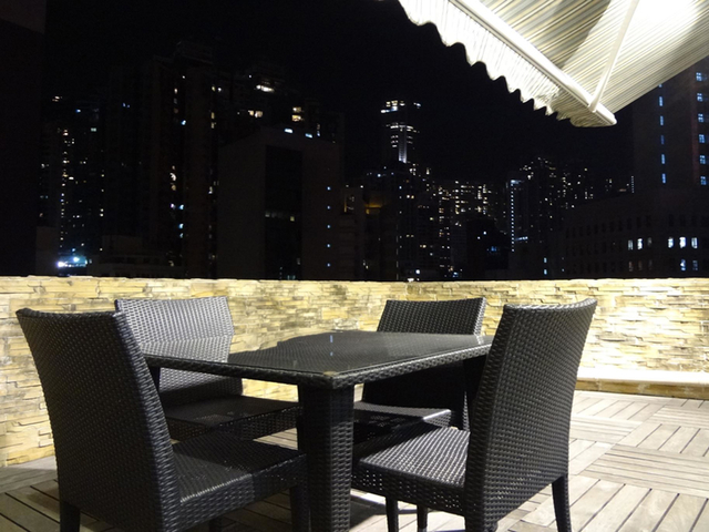dining table in alfresco area; hong kong night view