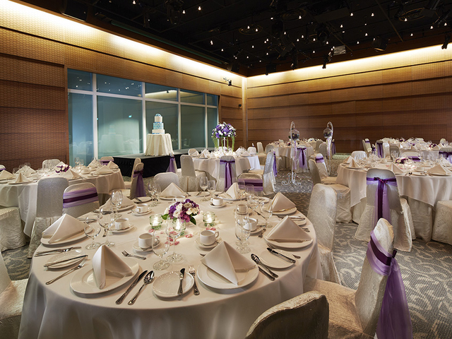 banquet wedding hall with white theme decorations and mini stage