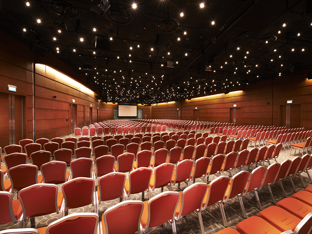 large seminar event space in singapore with big projector screen and red audience chairs