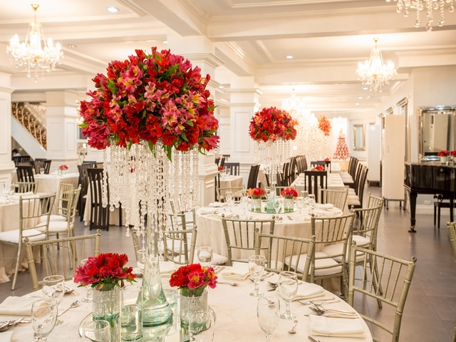 wedding ballroom with round table setup and high flower vase on each table