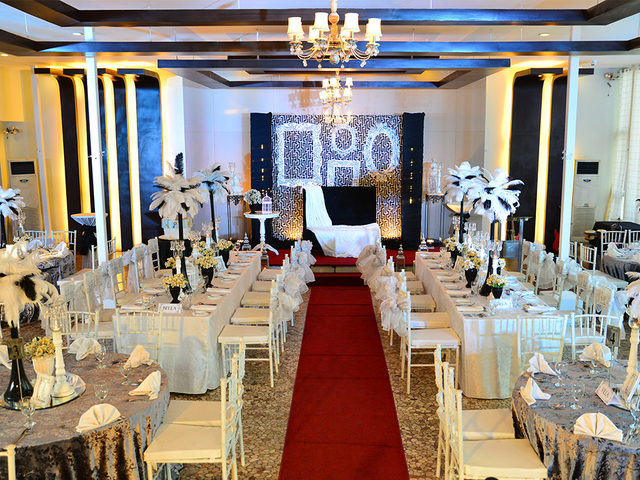 ballroom with red carpet at the middle of the room to the stage and gleaming chandelier