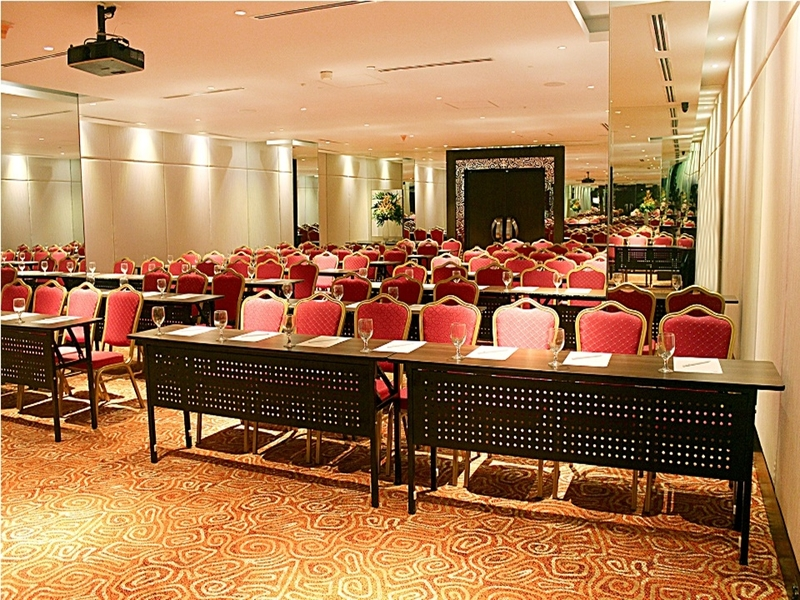 manila function hall with black long tables and red audience chairs
