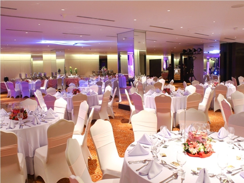 large wedding venue in manila with beige round tables set up and flower decorations