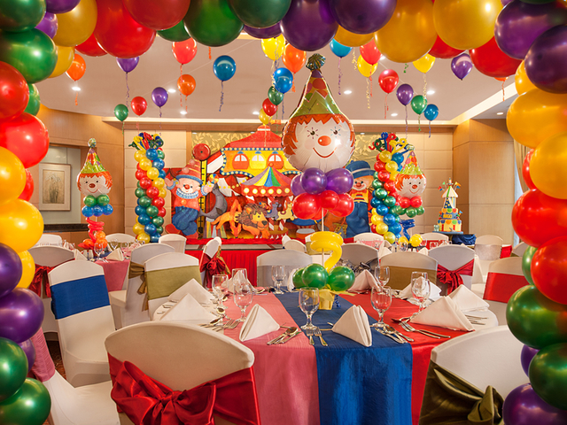 kids birthday party decorated with clowns and colourful balloons