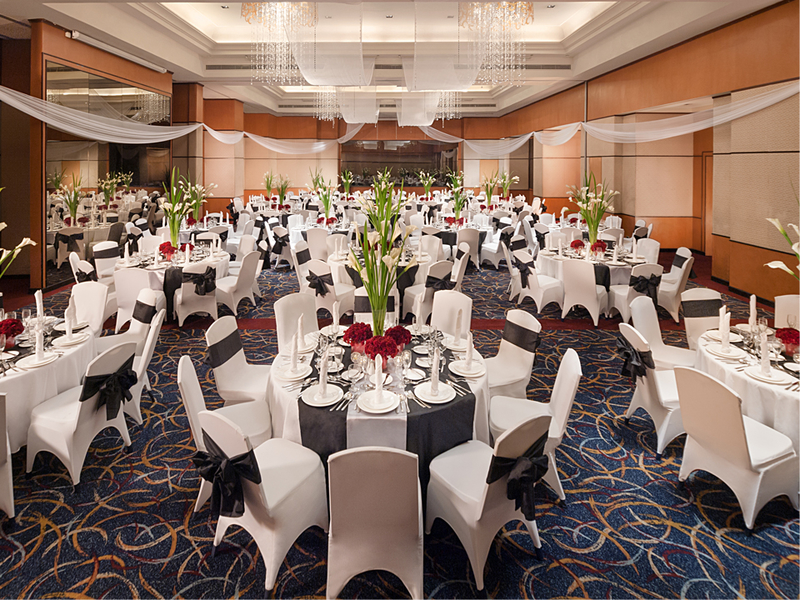 round table setup at hotel ballroom decorated with carpet and chandeliers