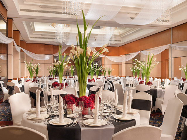 round table seating style with flower vase as the deoration of each table