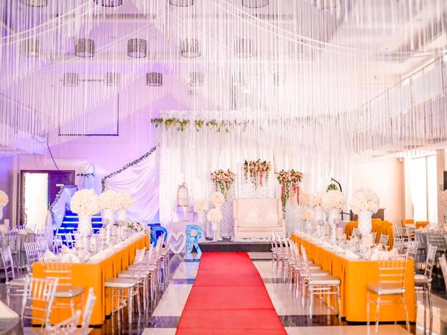 indoor wedding reception with long table setup and red carpet