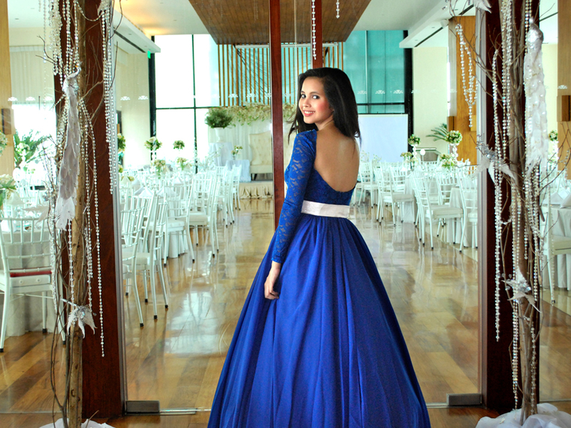 woman using blue long dress is posing in front of the function hall