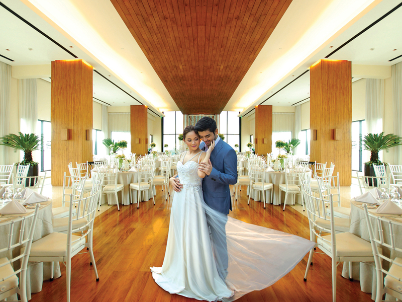 couples are doing their wedding photoshoot inside the hotel ballroom