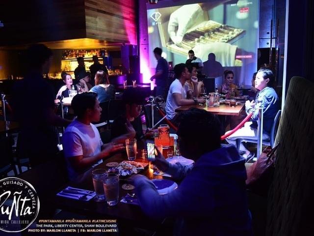 staff working behind bar; customers enjoying drinks in bar