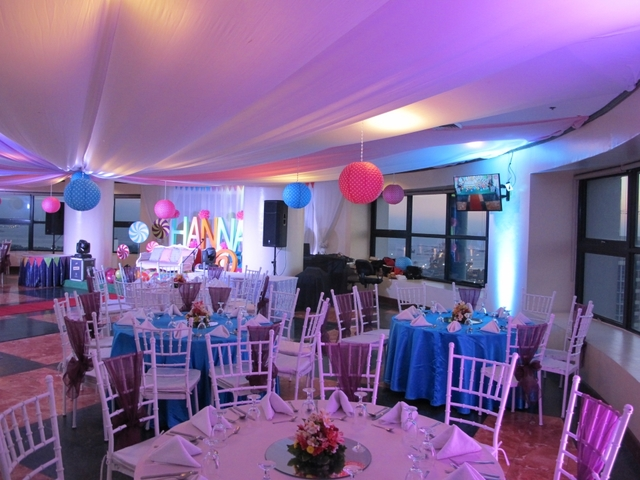 birthday party event space in manila with white round tables and colourful hanging decoration