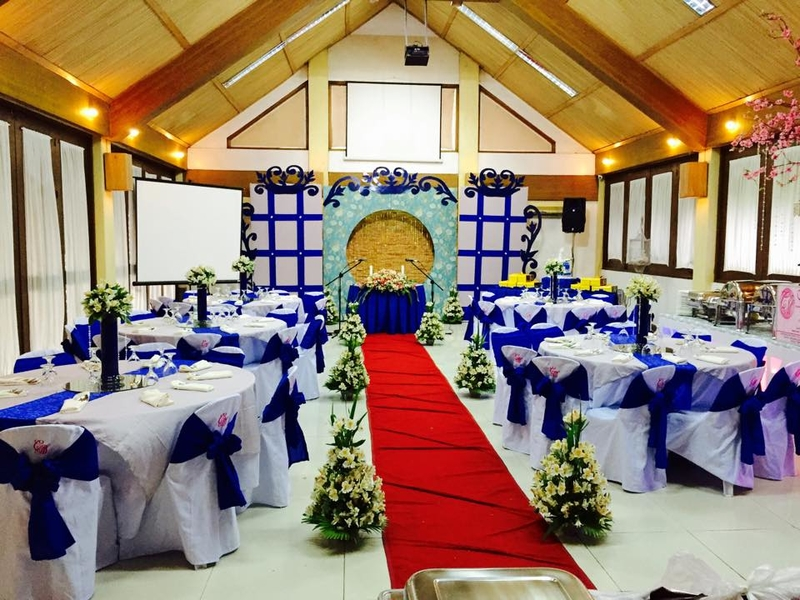 small wedding space with banquet seating and red carpet