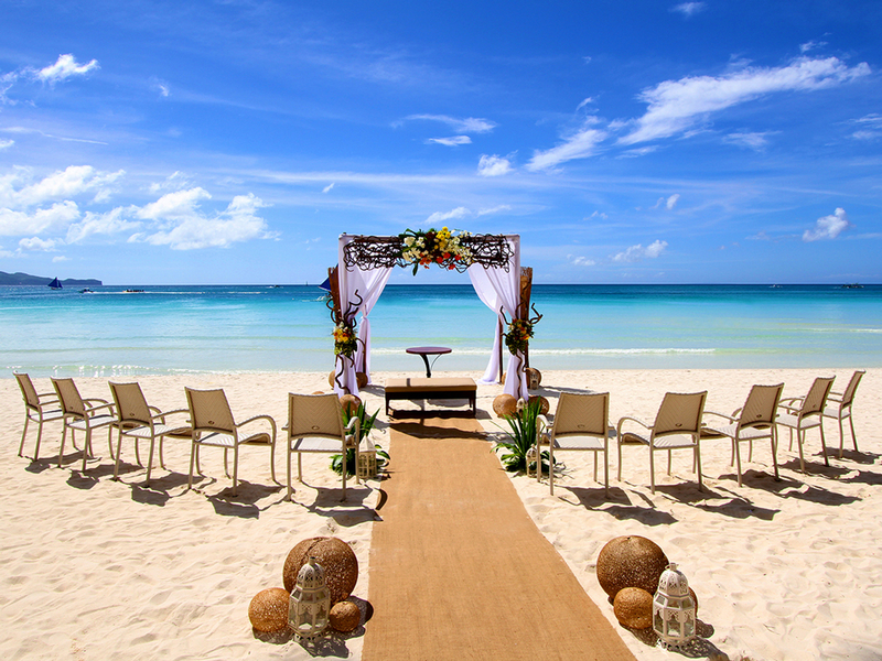 chairs lineup by beachside; wedding aisle; flower arch