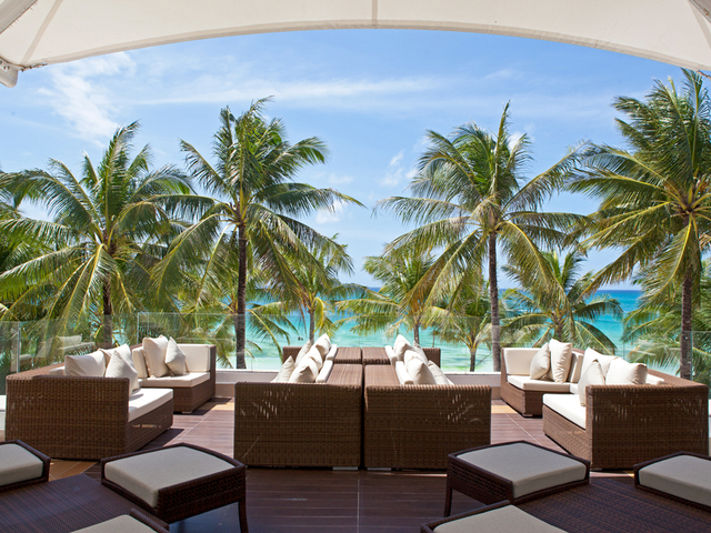 lounge chair overlooking beach area; coconut trees