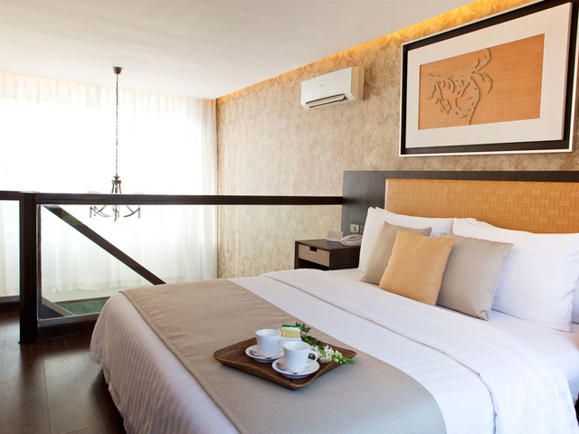 large hotel bed with breakfast tray on bed
