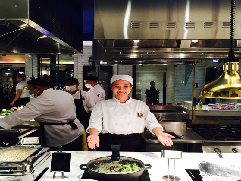 chefs are cooking behind the open space kitchen in makati restaurant