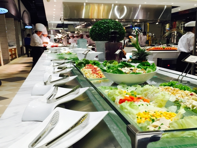 large buffet table in makati restaurant with several salad dishes