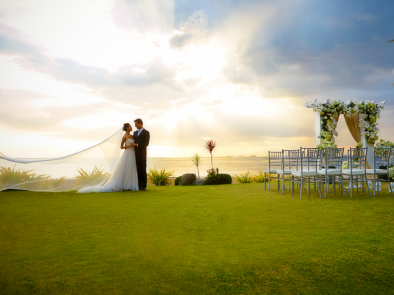 bridge and groom embracing next to garden wedding setup