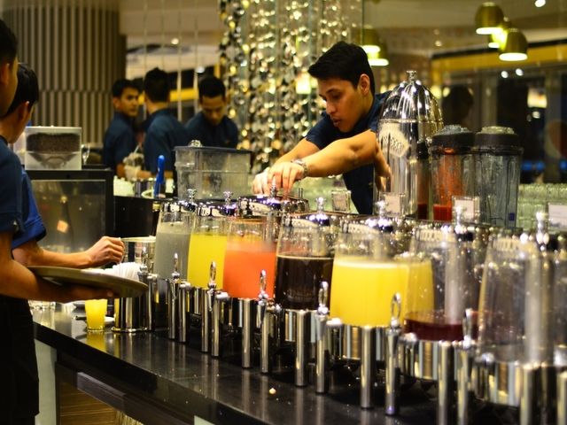 restaurant employees are refilling drinks at the buffet table