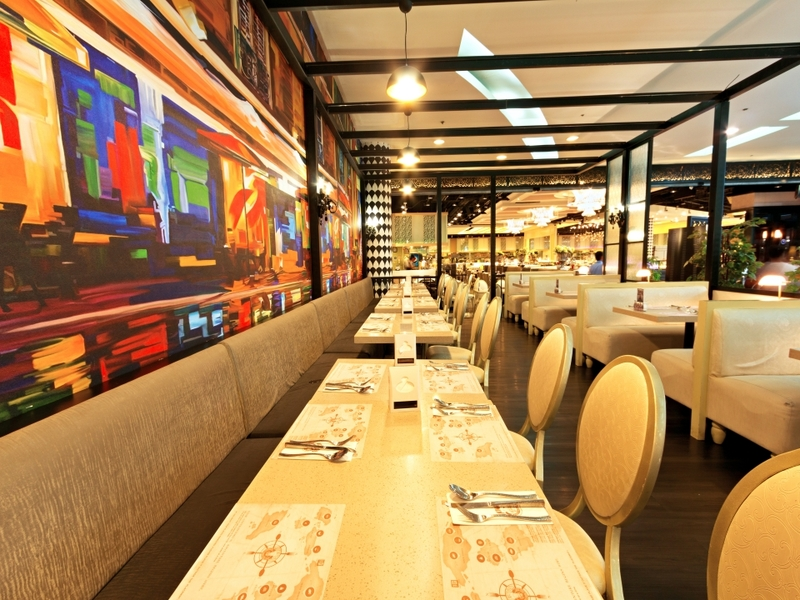 large dining room with several long table and wall painting in quezon city restaurant