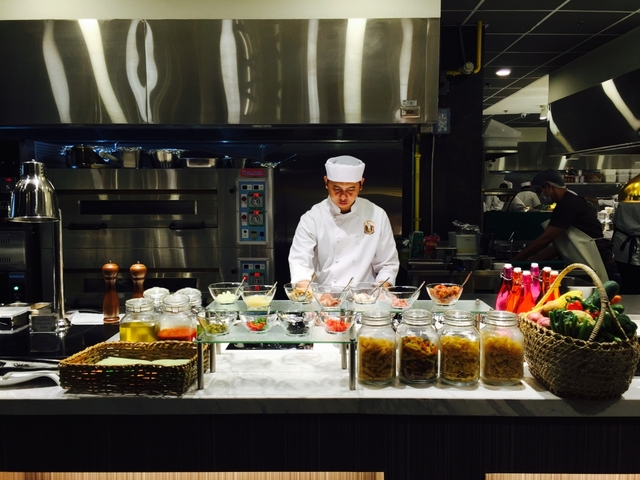 philippines restaurant's chef with white apron standing behind the buffet table