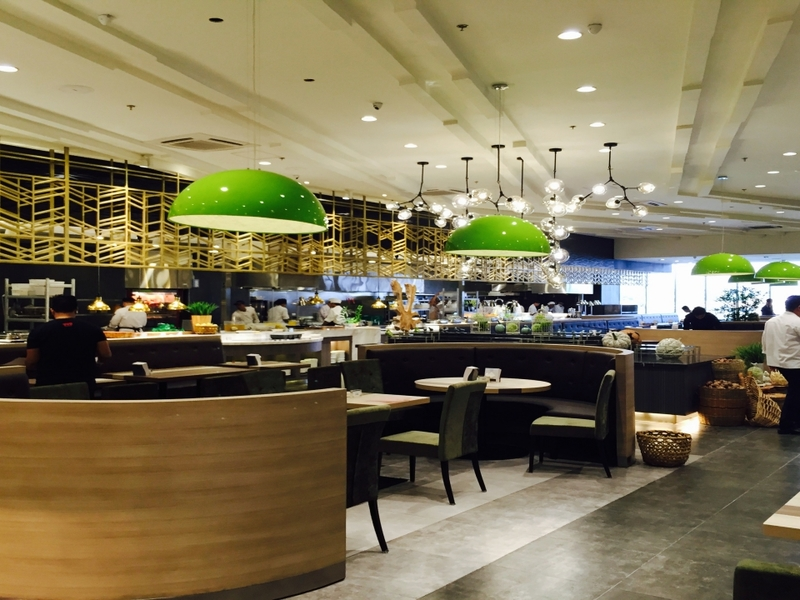 high ceiling event space in paranaque with round couches and green pendant lamps