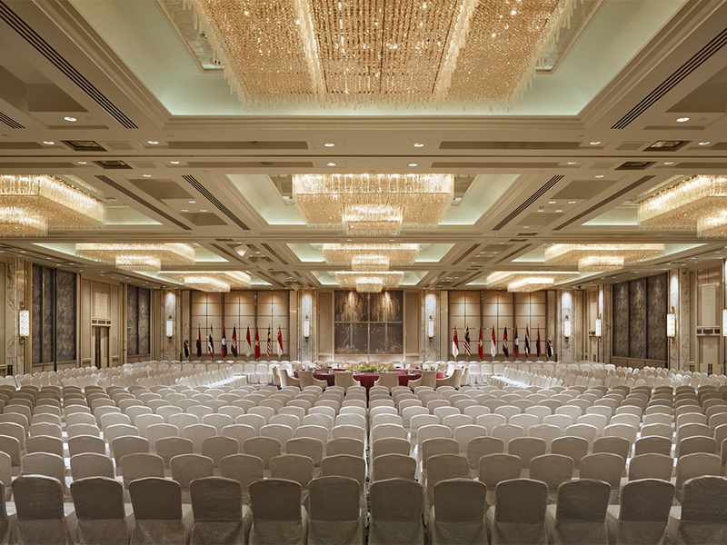 high ceiling ballroom with white audience chairs and crystal pendant lights