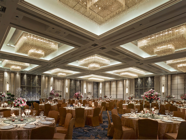 ballroom in singapore with brown round tables and crystal pendant lights