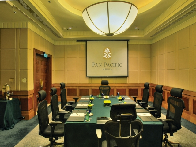 meeting room with chairs and projector screen on wall