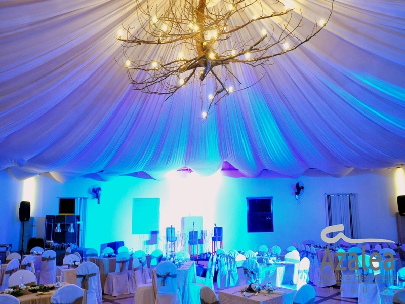 hall with banquet style setup, stage, and root lighting on the ceiling