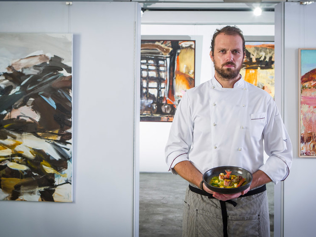 chef tosimo taddei crafts special dishes that reflect his heritage with the background of a lot of paintings on the wall