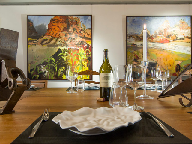 dining table equipped with a bottle of wine and cutlery facing to exquisite fine artworks