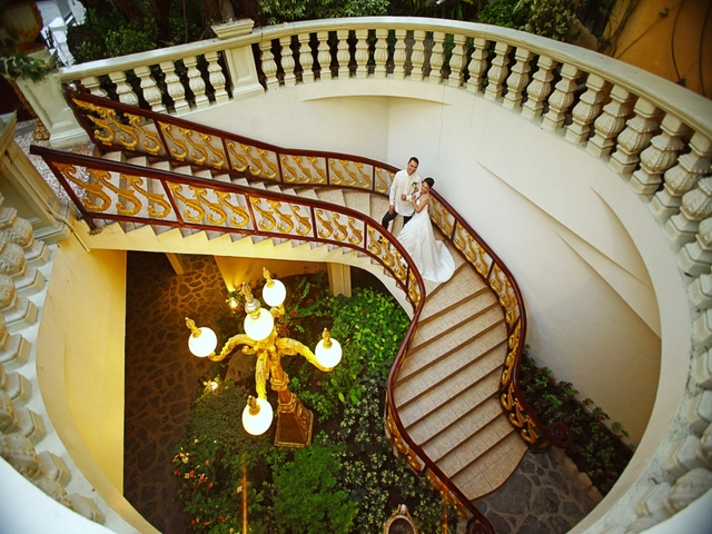 couple moving down spiral staircase