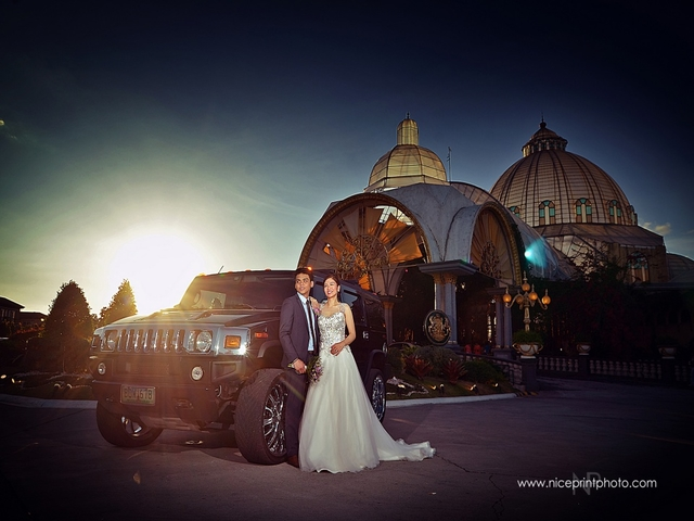 couple posing next to car during sunset