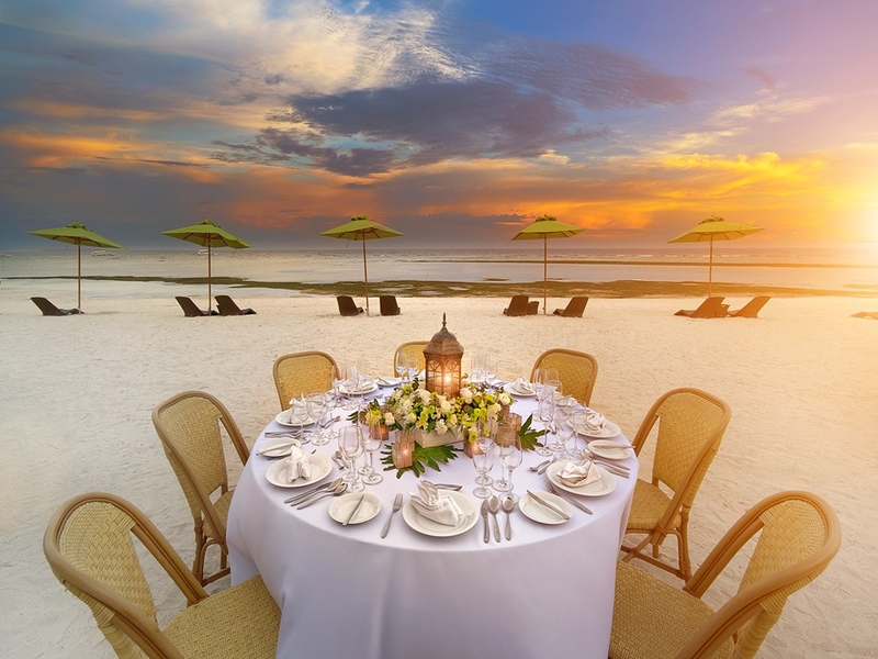 round table dining setup by the beach