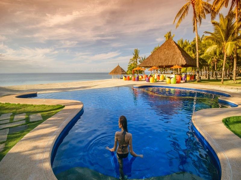 model swiming in outdoor pool overlooking sea