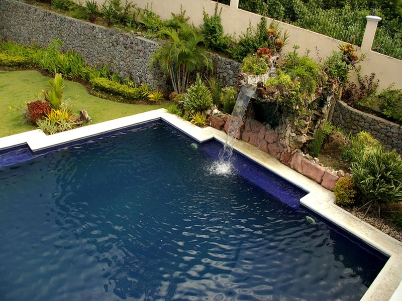 swimming pool and garden with small fountain