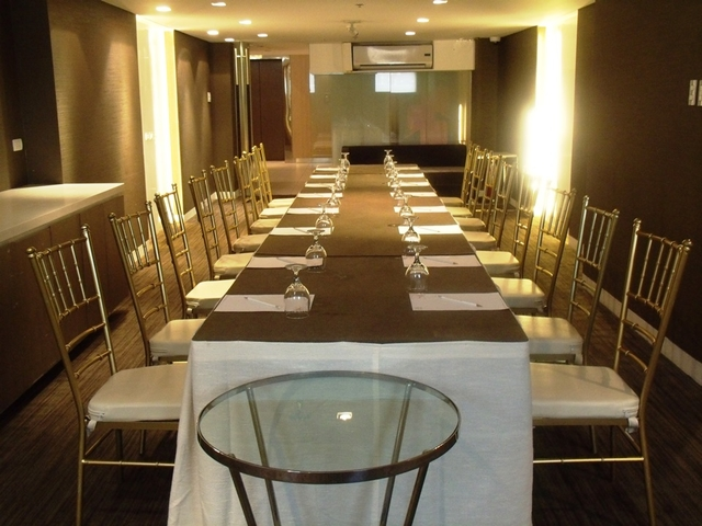 hotel private meeting room lined with chairs; side table