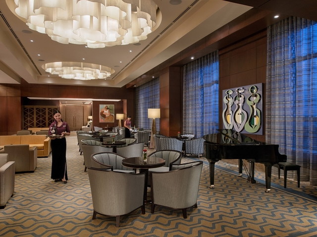 private business lounge area featuring gleaming chandeliers and grand piano