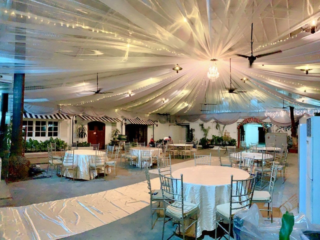 semi outdoor wedding with white satin carpet across the function hall
