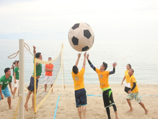 friends playing volleyball by the beach