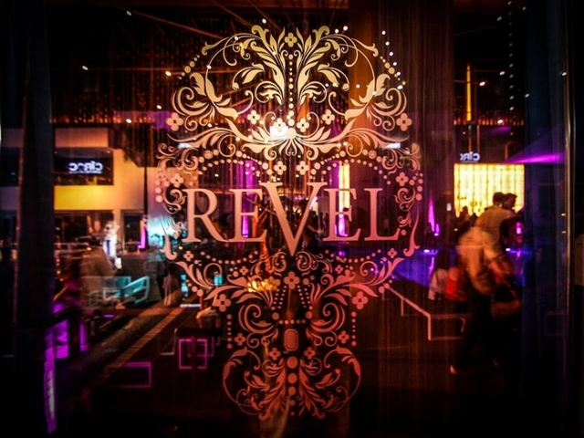 revel at the palace logo on glass wall