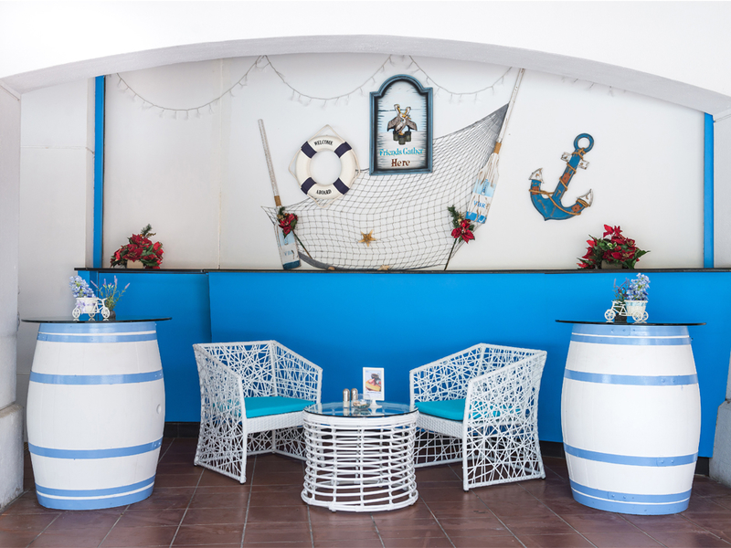 sea themed event venue in singapore with anchor decoration and white-blue barrel table