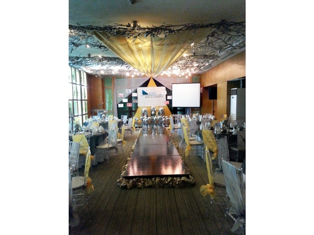 graduation party with long stage at the center of the room and balloon decorations