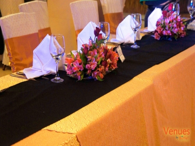 meeting table lined with tablecloth; flower arrangement