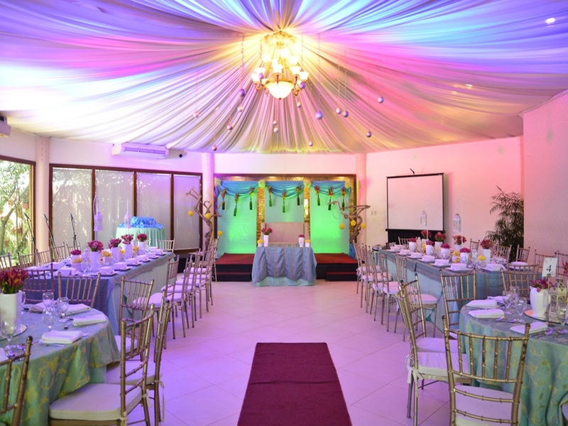 medium solemnization venue with long dining tables and pendant lamps