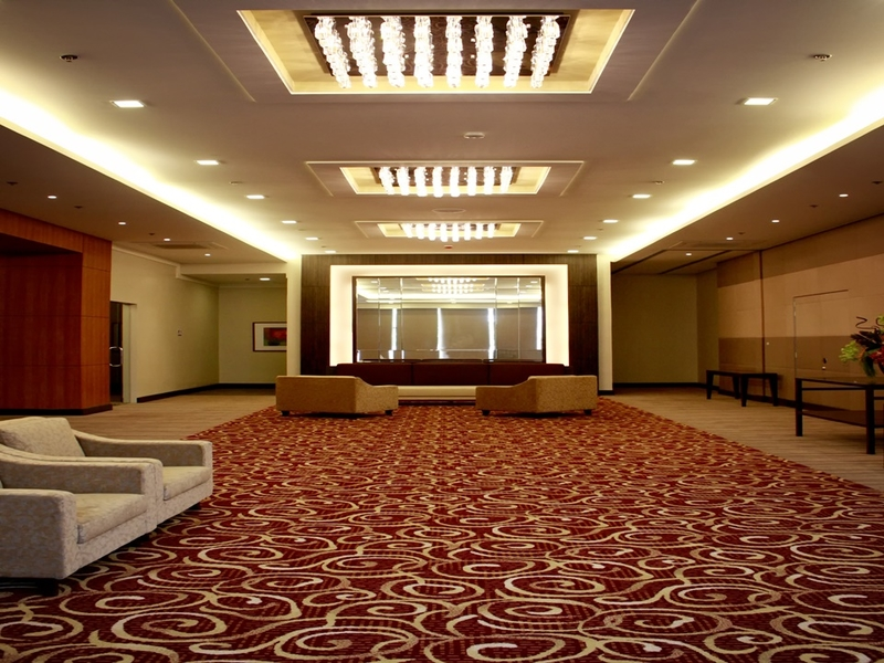 empty and spacious hotel ballroom equipped with audio-visual facilities and stage